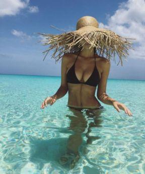 7. Emily Ratajkowski, model underneath an oversized straw